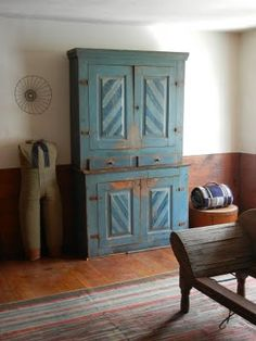 19th century grain painted cupboard in blue paint, hand woven Shaker rug