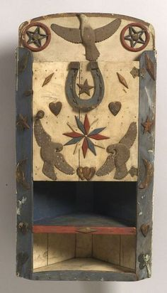 Red, White, and Blue Painted Pine Folk Art Hanging Corner Cupboard, America, late 19th/early 20th century, the cupboard with arched crest applied with a carved eagle figure flanked by stars