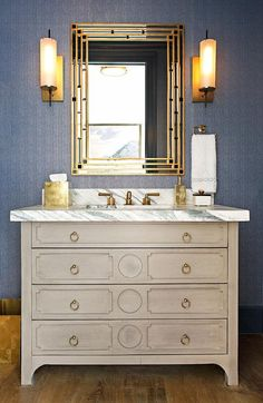 Matt Morrison Development - Gorgeous blue and gold powder room is equipped with a Wisteria Modern Gustavian Chest adorning brass ring pulls and a calcacatta marble countertop fitted with rectangular sink paired with a brass faucet positioned beneath a gold mirror flaked by Arteriors Stefan Sconces mounted on blue painted strie wallpaper.