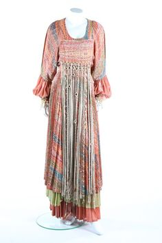 A good Bill Gibb printed lurex hippy peasant style evening gown, 1977. labelled, with an apron of silver macramé fringes falling from the bodice, multi-layered crystal pleated skirt, Murano glass beaded and fringed cuffs to match, bust 34inch.  This gown was one of the looks shown at Bill Gibb's ground-breaking 10th anniversary fashion show at the Royal Albert Hall in 1977.