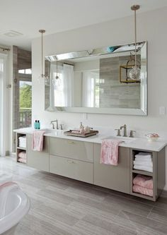 Stunning bathroom featuring a floating gray double vanity with a white quartz countertop accented with pink towels as well as his and her sinks underneath a large beveled vanity mirror illuminated by clear glass globe pendants atop gray staggered tiled floor.