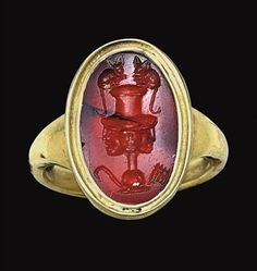 A  ROMAN CARNELIAN RINGSTONE   CIRCA 2ND CENTURY A.D.   The flat oval stone engraved with a tall two-handled krater, its body composed of a triple mask, one frontal flanked by two in profile, with handles formed from mice seated on the rim, a pedum and syrinx on either side of the foot; mounted as a ring in a modern gold setting   5/8 in. (1.6 cm.) long; ring size 6¾
