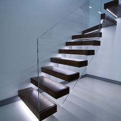 Floating stairs in dark finish. Led lights under each tread with opti- white glass balustrade.