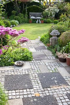 Decorative pathway leading to lawn and bench, Azalea in mixed border and dish of pebbles