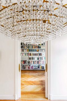 Everything about this chandelier and colorful bookcase makes us happy.