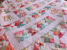 I love how the tight, intricate quilting on the white borders really makes the colors pop.