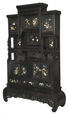A black lacquered Japanese cabinet, Meiji period, late 19th century, with stepped centre above two sliding doors, each overlaid with carved bone depicting birds and flowers, and two larger conforming doors to each side, above an arrangement of shelves each with lacquered rear panels, and carved and pierced panels below, the lower section with an arrangement of cupboards and drawers, also depicting flowers and birds in relief, against dark lacquer, on a carved pierced scroll base, 86''x 49''