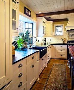 Country Kitchen with Terra cotta tile floor, Custom hood, Wood counters, Bay window, Soapstone counters, Flat panel cabinets