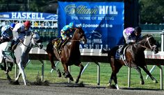Triple Crown winner American Pharoah with jockey Victor Espinoza, center, goes by the stands for the first time Sunday Aug. 2, 2015 at Monmouth Park in Oceanport, N.J. on his way to an easy win in the 48th running of The Haskell Invitational. Skip Dickstein Photo