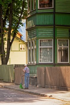 Man With A Green Brush - An old man brushing the street in the Kadriorg area of Tallinn, Estonia. His brush matches the color of the house and the fence.