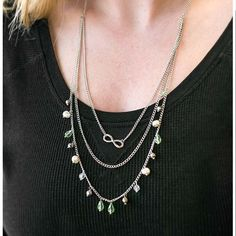 A silver strand adorned with a glistening infinity symbol gives way to layers of silver chain. Complemented with matching silver beading, the lowest chain is decorated with pearlescent pebbles and crystal beads featuring a translucent green hue for a splash of shimmery color. Features an adjustable clasp closure.  Includes one pair of matching earrings.