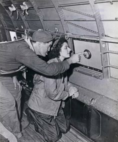 Ensign Jane Kendeigh, a Navy flight nurse, peers through a porthole in the cabin of a C-54 Navy transport plane as Chief Pharmacist Mate Silas V. Sturtevant of Napa, California, points out important land marks on Iwo Jima. She flew to Iwo Jima on 03/06 to be the first Navy flight nurse to put foot on the battlefield. She supervised the loading of wounded Marines aboard the big planes and then cared for the wounded on their trip back to a base hospital in the Marianas ~