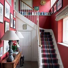 Modern Rustic Red Hallway with Striped Runner in Hallway Ideas. The hallway, staircase & landing in a modern rustic farmhouse. Red walls hung with framed artworks and staircase bookshelf. Hallway Colour Schemes, Hallway Colours, Interior Staircase, Staircase Landing, Staircase Bookshelf, Striped Carpets, Striped Carpet For Stairs, Hallway Paint, Flur Design
