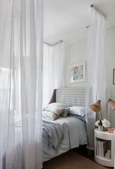 Space Saver DIY Ideas + Projects For Studio Apartments | Apartment Therapy - Surrounding your bed in sheer curtains provides a veil of privacy (and discourages guests from sitting on it), while still leaving your apartment visually open and accessible. Separate and simple seating areas can be nearby.