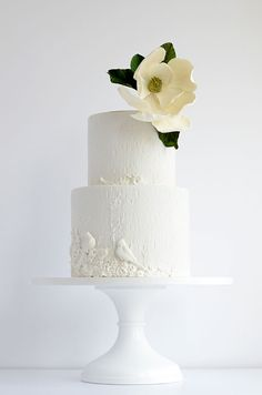 White wedding cake with a textured surface adorned with birds and a single handmade magnolia by Maggie Austin