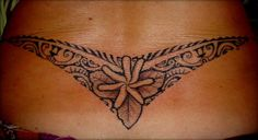 "Tattoo on Lower Back of Maori Polynesian style for Women representing a ""v"" or boomerang with a flower and leaves in the center and the wings fullfilled with multiple ancient symbols from the Traditional Marquesas's Ancient TATAU. Designed & Tattooed by Manao Tiki Tattoo Toulon"