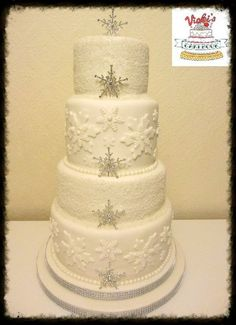 four tier round white wedding cake decorated with snowflakes pearls shimmer and diamante snowflakes for a winter wedding Winter Snowflake Wedding Cake
