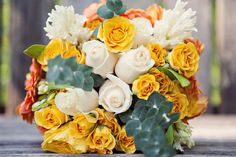 Colorful bouquet. yellow and orange. White and yellow roses, orange daisies. Would be great for a fall wedding bouquet. The groom put it together the morning of the wedding :)