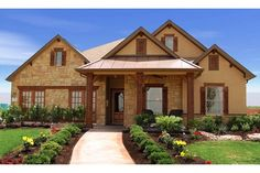 A lushly landscaped walk leads to a new home with timeless style built by Wilshire Homes in the Pecan Crossing community. New Braunfels, Texas