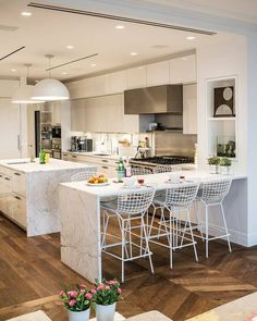 Kitchen features unique use of marble on not just countertops, but side detail, with slick white cabinetry and half-sphere chandeliers over island.