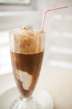 The quintessential summer treat, a root beer float, with scoops of vanilla ice cream floating in bubbly foamy root beer.