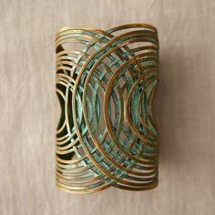"""This statement cuff is crafted from coiling strands of oxidized brass wire. Inspired by organic design and traditional Latin American crafts, each Sibilia piece is made by hand in the Abasto district of Buenos Aires, Argentina.- Oxidized brass- Nickel and lead free- Adjustable- Handmade in Argentina4""""H, 2.5"""" diameter"""