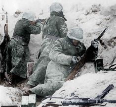 A group of German Waffen SS infantrymen fire at Allied positions in a little town in Bastogne, Winter 1944.