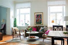 Sala de estar coloridinha com mistura de estilos, iluminada, separada de outro ambiente
