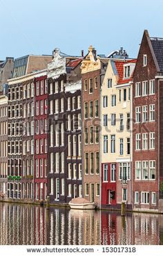 Row of ancient canal houses in the Dutch capital city Amsterdam with a canal in front