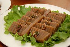 도토리묵(dotorimuk) / Acorn Jelly Salad  Acorn jelly salad mixed with carrot, cucumber, chili, and suk-gat (edible chrysanthemum). It is dressed with a soy sauce seasoning.