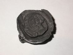 Cloth seal from Venice, Italy, stamped with the lion of St Mark. Lead seals were attached to bales of cloth for quality control. They provide details about the fabric: brand name, size and source, as well as the maker's personal mark. This seal was attached to linens or cottons imported from Europe and indicates the important role London played in the international textile trade.  Production Date: Late Medieval; early 15th century