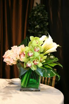 The modern, medium height floral arrangement is designed with green, Cymbidium orchids