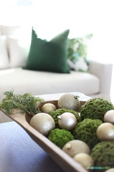 Large wood dough bowl filled with mossy greenery and gold ornaments.