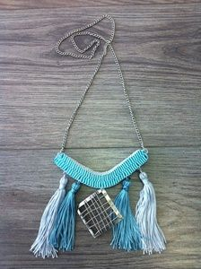 A unique necklace from my collection with two colors ribbons light blue and silver.There is a silver geometrical shape in the middle , two colors tassels and silver chain.