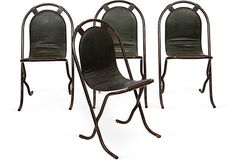 Set of four stylish chairs with steel arched-back frames and vinyl seats.