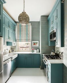 Small kitchen layout with painted cabinets and oversized sink. Wish that sink was in front of the window but sometimes you just have to work with what you have. Love the cabinets