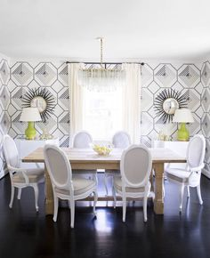 A simple, unfinished farm table counterbalances the dining room's bold geometric wallpaper.