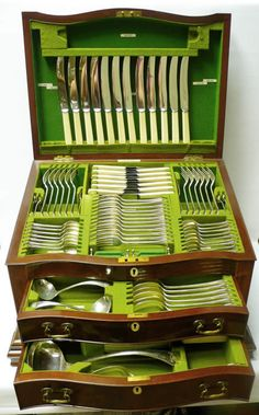 "Silver Canteen of Cutlery in a Box - waxantiques An outstanding item. A comprehensive set of sterling silver cutlery for 12 people in an attractive plain style with scalloped ends. Total 109 silver pieces plus a set of 12 dinner and dessert knives. Each piece (excluding knives and fish cutlery) has an engraved crest and motto ""Nil Sine Labore"". All in a marvellous fitted wooden box in the form of a miniature bureau with inlays and serpentine   Sheffield 1913-1924, maker Henry Atkins"