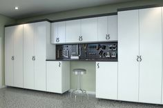 A neat look is achieved in this garage where enclosed white melamine cabinets line up against an entire wall. Featured in the middle is an open tool storage where a workbench stands below. Diy Garage Storage Cabinets, Garage Cupboards, Garage Storage Solutions, Garage Shelving, Garage Shelf, Diy Cabinets, Storage Ideas, Garage Organization, Organization Ideas