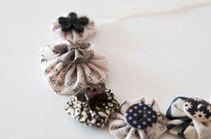 Joli collier vintage en tissu composé de 5 yoyos et 5 boutons originaux, cousu sur ruban en satin, par la créatrice lyonnaise Coquelicocotte