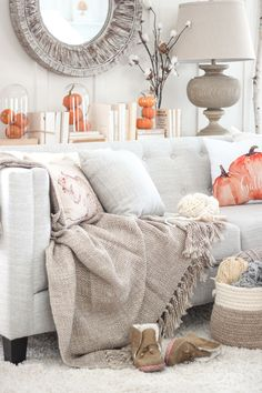 Lucy loves neutrals and whites, but she cleverly incorporated orange in her fall decor. Behind the couch, clear domes contain trios of pumpkins, which are situated among chic, coverless books. - GoodHousekeeping.com