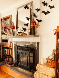 Rather than confining her Halloween decor to a narrow mantel, photographer Lindsey Ocker expanded her decorations by adhering bats and cobwebs to the surrounding walls and bookcase. See more at Lindsey Ocker Photography.    - Redbook.com
