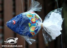 Fish in cellophane using plastic bag, colored napkins (maybe tissue paper), rubber band, and scissors.