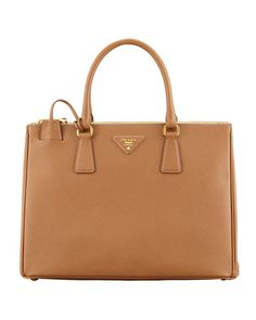 """Saffiano calfskin leather. Golden hardware. Double tote handles with rings, 5"""" drop. Removable, adjustable shoulder strap, 37""""L. Front and back zip compartments frame open top. Expandable snap sides."""