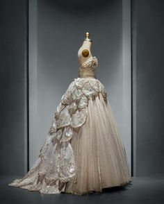"Christian Dior - Venus"" Evening Gown, fall/winter 1949-50.  Machine–sewn, hand–finished gray silk taffeta and tulle; hand–applique of gray silk tulle and horsehair petals, hand–embroidered with opalescent, gold, and silver gelatin sequins, feather paillettes, synthetic pearls, and clear crystals."