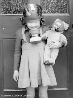 WWII, Norfolk.England. With acute food rationing, most of the population lived off the land. Unfortunately, this little girl lived almost entirely on a diet of Brussels sprouts. Even her Teddy Bear needed a gas mask!