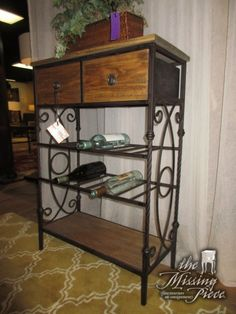 "Small rustic wine bar in a medium finish with bronze metal sides. There are two drawers, with two wine racks and one shelf below. Each rack holds six bottles. 25""wide x 12""deep x 37""high."