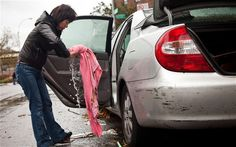 A woman wrings water out of a towel while cleaning her flooded car, caused by Hurricane Sandy, in the Lower East Side of New York City - Picture: Andrew Burton/Getty Images