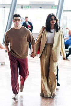 Nick Jonas & Priyanka Chopra End Their Stylish Weekend In Cannes: Photo Nick Jonas and Priyanka Chopra walk hand in hand while heading to their terminal on Sunday (May in Nice, France. The couple kept up their style with a more… Nick Jonas, Couple Style, Priyanka Chopra, Cannes, Airport Attire, Striped Sandals, Red Trousers, Fashion Couple, Girl Fashion