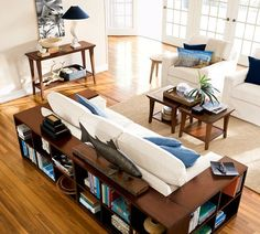 Bookshelf wrapped around the couch-- I want to look at the backside of a sectional with this idea :)